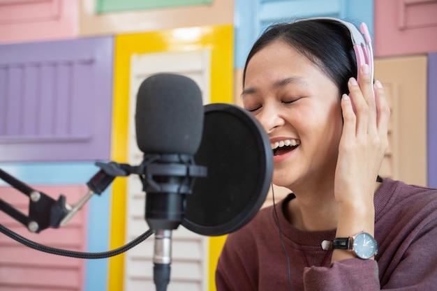 Close de uma garota usando fones de ouvido na frente de um microfone