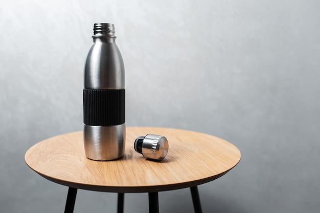 Close de uma garrafa de água térmica reutilizável de aço e uma lata na mesa de madeira