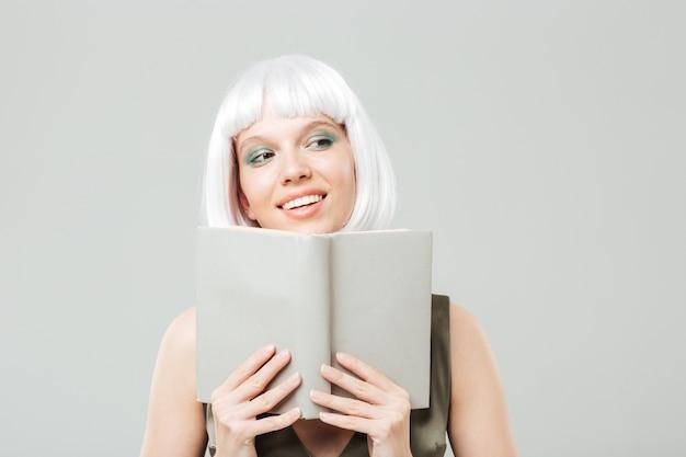 Close de uma jovem adorável e feliz com uma peruca loira, sorrindo e lendo um livro