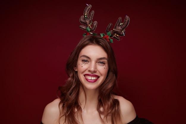 Close de uma jovem alegre mulher de cabelos castanhos com maquiagem festiva usando chifres na cabeça em pé, sorrindo e expressa emoções positivas verdadeiras