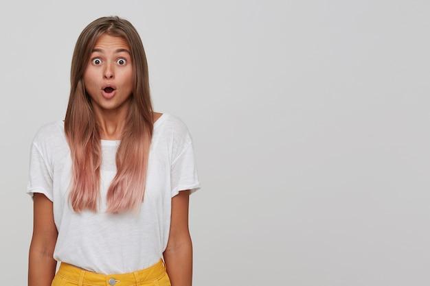 Close de uma jovem atordoada e atônita com cabelo longo tingido de rosa pastel usa uma camiseta em pé com a boca aberta e se sente espantada isolada sobre uma parede branca com copyspace para sua publicidade