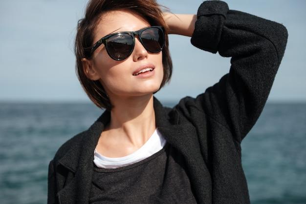 Close de uma jovem bonita e feliz com óculos de sol em pé à beira-mar