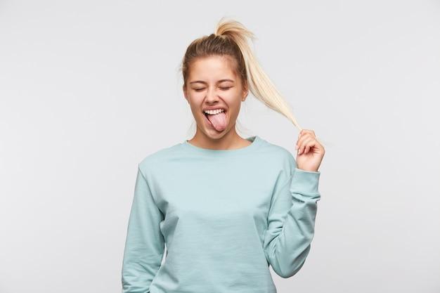 Close de uma jovem bonita e infeliz com cabelo loiro e rabo de cavalo usando uma camiseta azul