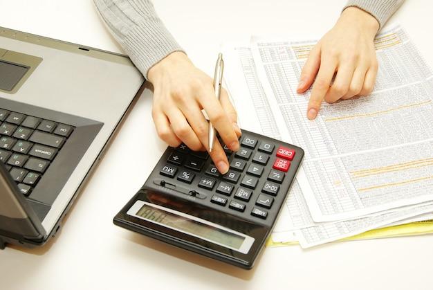 Close de uma jovem calculando contas