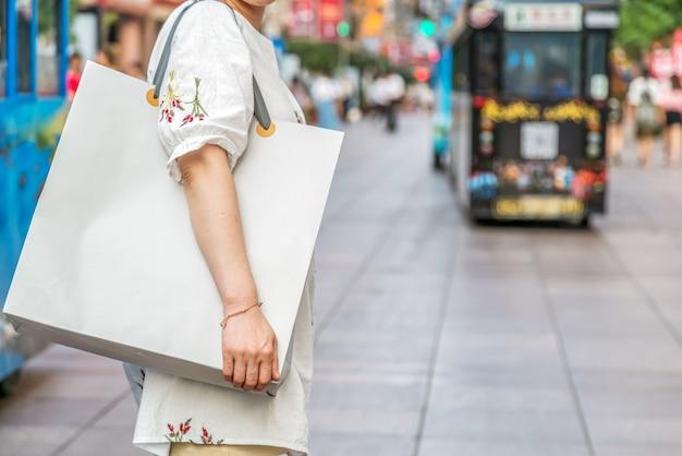 Close de uma jovem carregando sacolas de compras enquanto caminha pela rua