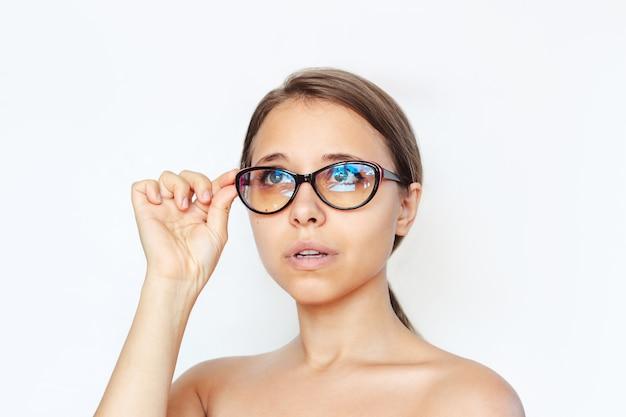 Close de uma jovem com óculos para trabalhar em um computador com lentes de filtro azuis