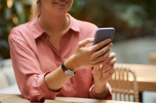Close de uma jovem digitando uma mensagem online em seu smartphone