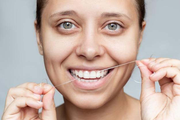 Close de uma jovem e bela mulher caucasiana passando fio dental, dentes, higiene bucal, saúde bucal