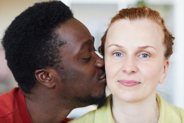 Close de uma jovem enquanto um homem africano beijando sua bochecha