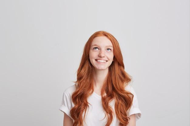 Close de uma jovem espantada com raiva e cabelo ruivo comprido e ondulado