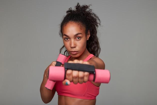 Close de uma jovem esportista morena de olhos castanhos, de pele escura, levantando as mãos com agentes de ponderação e olhando atentamente, posando