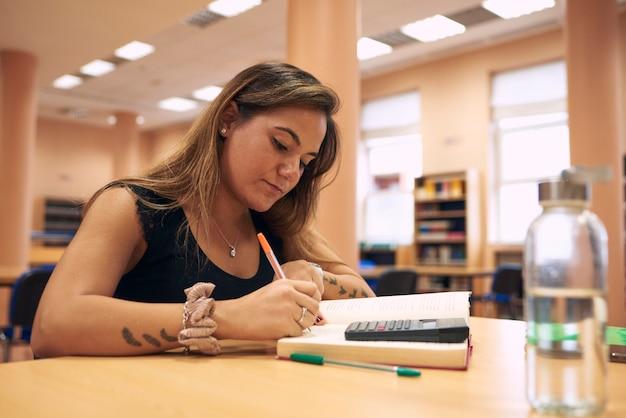 Close de uma jovem estudando em uma biblioteca