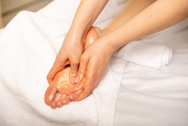 Close de uma jovem fazendo massagem nos pés Foto Premium