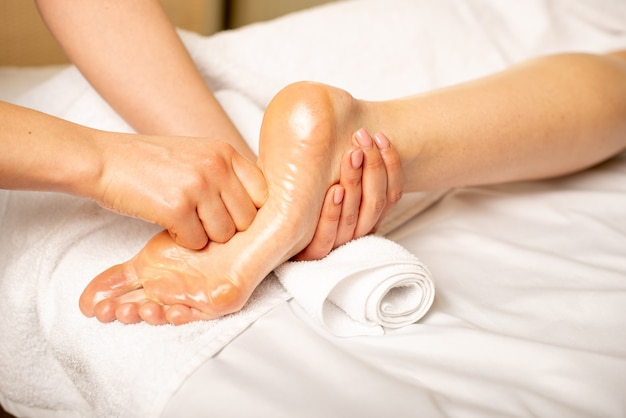 Close de uma jovem fazendo massagem nos pés