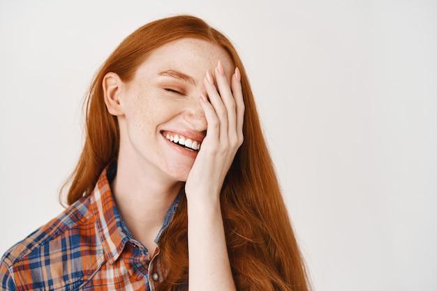 Close de uma jovem feliz com cabelo ruivo natural e pele pálida, sorrindo alegremente e cobrindo metade do rosto, em pé sobre uma parede branca