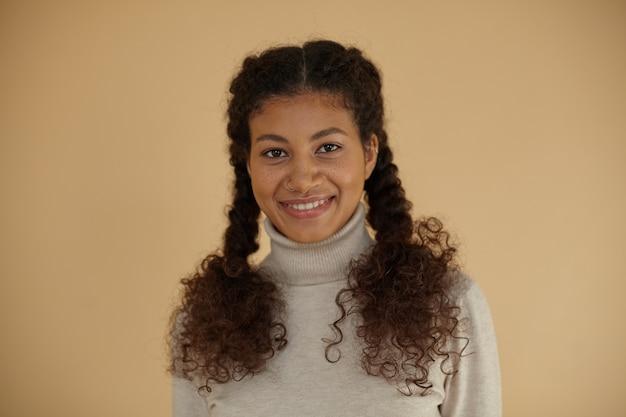 Close de uma jovem fêmea de pele escura e cacheada com tranças, sardas no rosto e maquiagem natural, enquanto posava sobre um fundo bege em um suéter de lã
