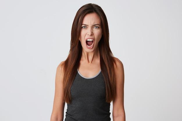 Close de uma jovem furiosa com cabelo comprido e boca aberta, irritada e gritando