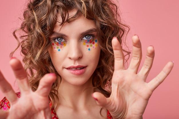 Close de uma jovem glamourosa de olhos azuis com um penteado festivo e pontos multicoloridos no rosto, mordendo o lábio inferior enquanto posava com as palmas das mãos levantadas