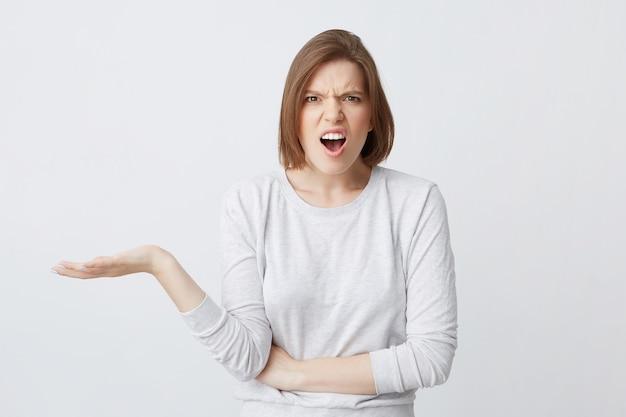 Close de uma jovem irritada e envergonhada de manga comprida parece confusa