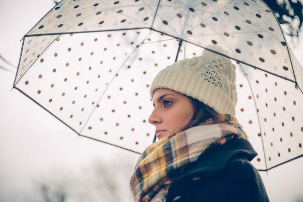 Close de uma jovem linda sob um guarda-chuva em um dia chuvoso de outono