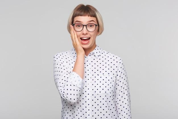 Close de uma jovem loira bonita e pensativa usando uma camisa de bolinhas