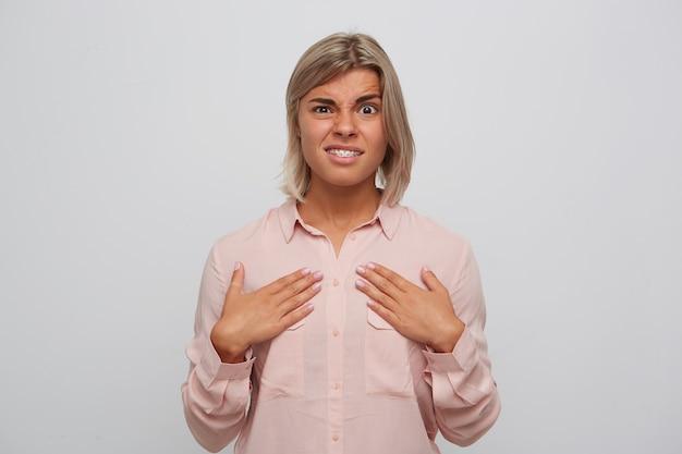 Close de uma jovem loira descontente e infeliz com aparelho nos dentes e usa uma camisa rosa parece confusa e aponta para si mesma com as mãos isoladas sobre a parede branca