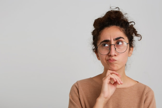 Close de uma jovem loira descontente e infeliz vestindo uma camisa de bolinhas, sentindo-se insatisfeita e mostrando um gesto de polegar para baixo isolado sobre a parede azul