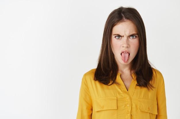 Close de uma jovem mostrando a língua e decepção, franzindo a testa, chateada, olhando para algo nojento, expressa antipatia em pé sobre uma parede branca.