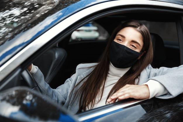 Close de uma jovem motorista sentada no carro com uma máscara facial