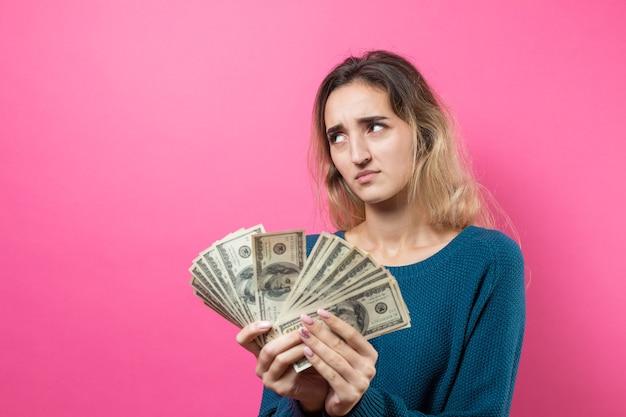 Close de uma jovem mulher bonita com um suéter azul de óculos e com o dinheiro dos dólares americanos na mão