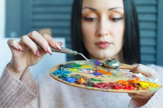 Close de uma jovem mulher com cabelo preto mistura tinta em uma paleta com uma espátula contra uma tela branca