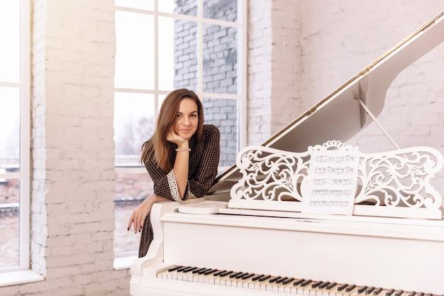 Close de uma jovem mulher em um vestido marrom, inclinando-se sobre um piano