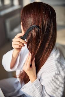 Close de uma jovem mulher penteando o cabelo