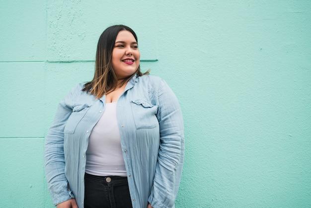 Close de uma jovem mulher plus size sorrindo em pé contra uma parede azul claro ao ar livre