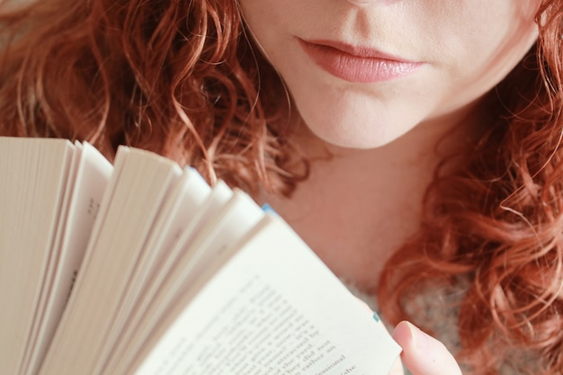 Close de uma jovem mulher ruiva segurando um livro sob as luzes