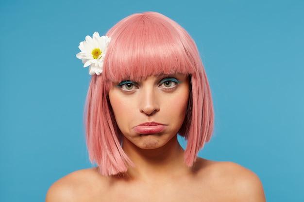Close de uma jovem ofendida, de olhos verdes, cabelo curto rosa e maquiagem festiva, contorcendo a boca enquanto parece triste
