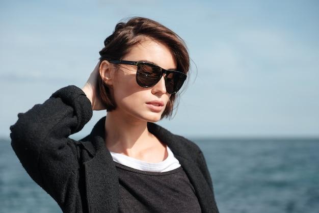 Close de uma jovem pensativa e atraente de óculos escuros na praia no outono