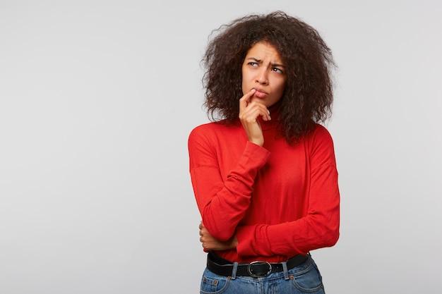 Close de uma jovem pensativa e duvidosa com um penteado afro escuro para o canto superior esquerdo