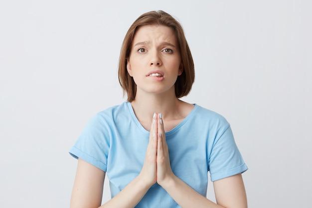 Close de uma jovem preocupada com a camisa azul e as mãos cruzadas em posição de oração