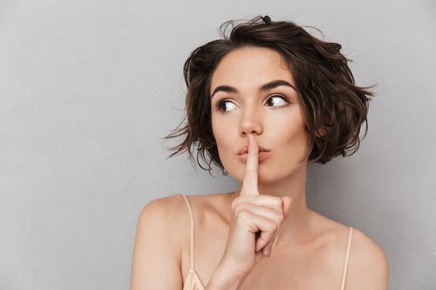 Close de uma jovem preocupada mostrando gesto de silêncio