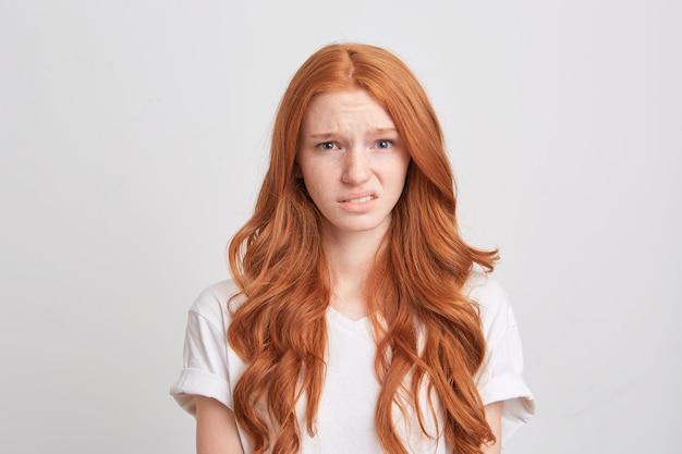 Close de uma jovem ruiva bonita com cabelo comprido ondulado e sardas usa camiseta e se sente triste e olha diretamente para a frente isolada sobre a parede branca