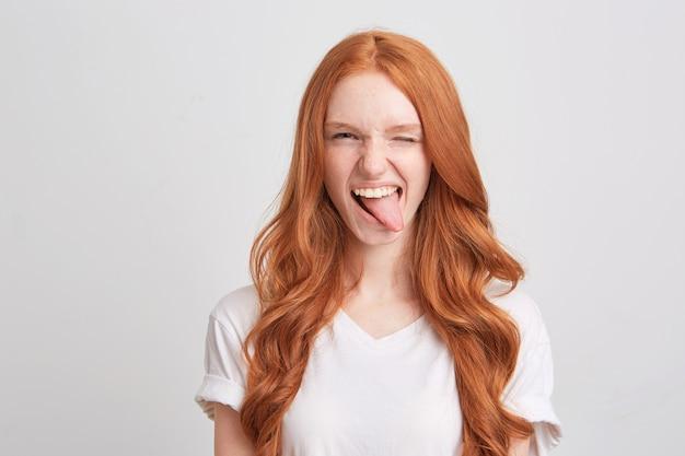 Close de uma jovem ruiva bonita com cabelo comprido ondulado e sardas usa uma camiseta triste e olha para a frente isolada sobre uma parede branca