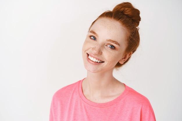 Close de uma jovem ruiva com sardas e olhos azuis tocando a pele limpa, sem maquiagem e sorrindo, em pé com uma camiseta rosa encostada na parede branca