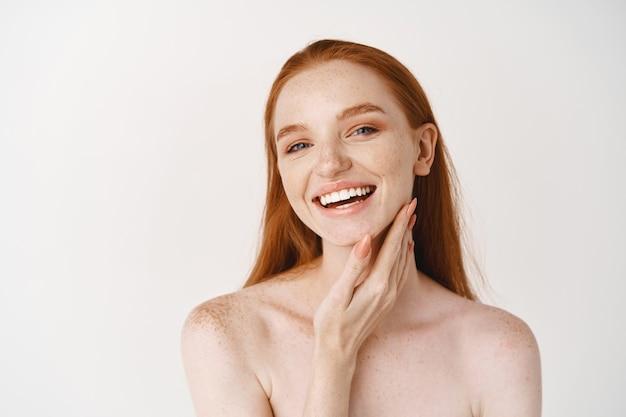Close de uma jovem ruiva linda sorrindo para a frente, tocando uma pele perfeitamente limpa no rosto e parecendo feliz, em pé nua sobre uma parede branca
