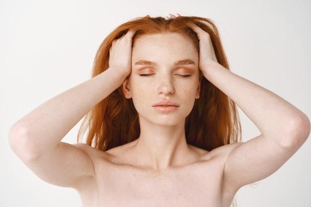 Close de uma jovem ruiva relaxada com pele pálida e sardas, massageando cabelos ruivos naturais com os olhos fechados, em pé, nua, sem maquiagem, na parede branca