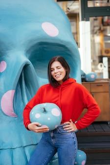 Close de uma jovem segurando uma abóbora ornamentada de cor azul em manchas brancas
