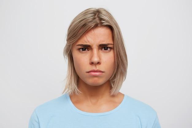 Close de uma jovem séria preocupada com cabelo loiro, usa uma camiseta azul e se sente estressada