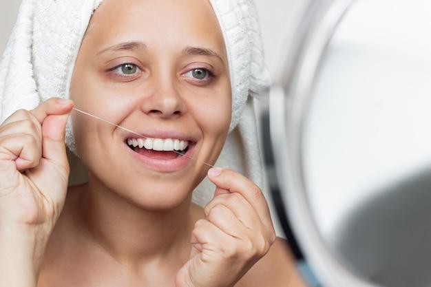 Close de uma jovem sorridente e alegre com uma toalha branca e fio dental, olhando no espelho