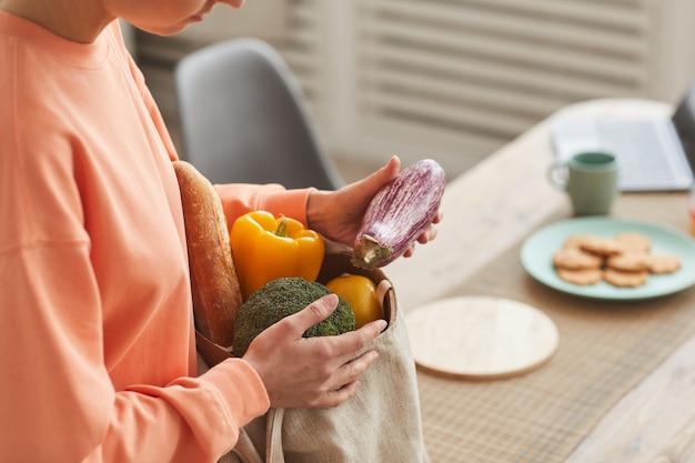 Close de uma jovem tirando os legumes frescos de um saco de papel na cozinha