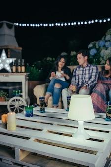 Close de uma lâmpada branca sobre uma mesa de paletes em uma festa ao ar livre com pessoas conversando ao fundo